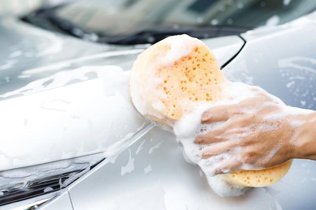 Ludzie pracownik mężczyzna trzyma rękę żółtą gąbkę i okno pianka do mycia bąbelków do mycia samochodu. myjnia samochodowa koncepcyjna czysta. zostaw miejsce na pisanie wiadomości.