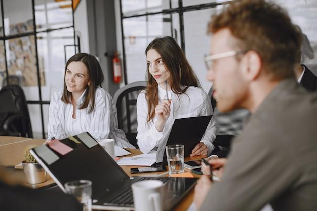 Ludzie pracują nad projektem. mężczyzna i kobiety w garniturach, siedząc przy stole. biznesmeni używają laptopa.