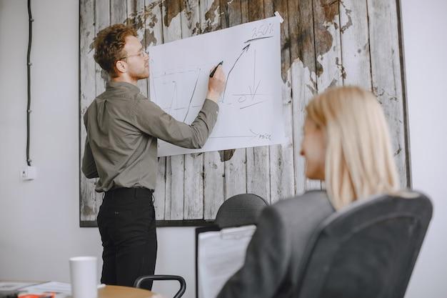 Ludzie pracują nad projektem. mężczyźni i kobiety w garniturach siedzą przy stole. biznesmen rysuje wykres na stojaku.