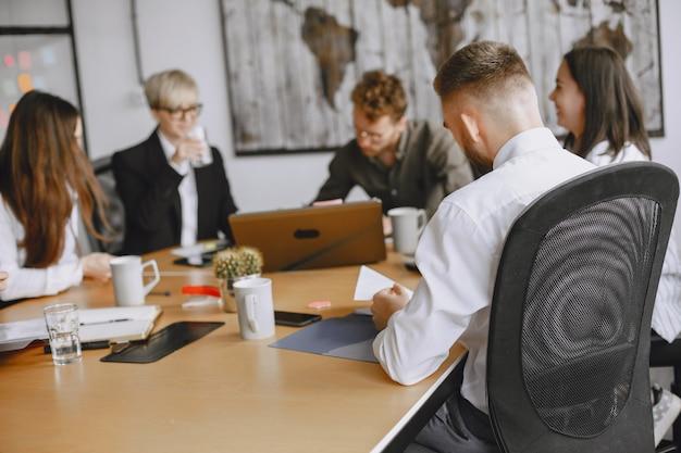 Ludzie pracują nad projektem. mężczyźni i kobiety w garniturach siedzą przy stole. biznesmeni używają laptopa.