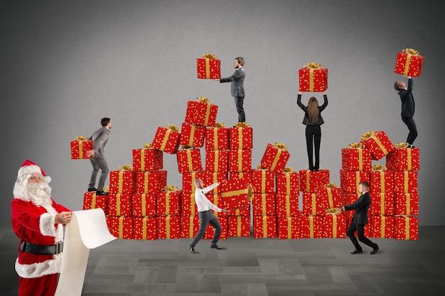 Ludzie pracują razem, aby naprawić prezenty świąteczne, podczas gdy święty mikołaj czyta listę prezentów