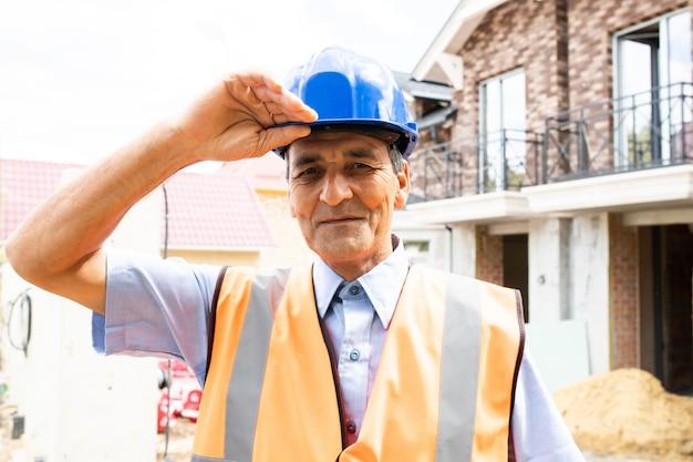 Ludzie pracujący na budowie portret szczęśliwy indyjski człowiek w pracy w nowym domu profesjonalny budowniczy robotnik latino
