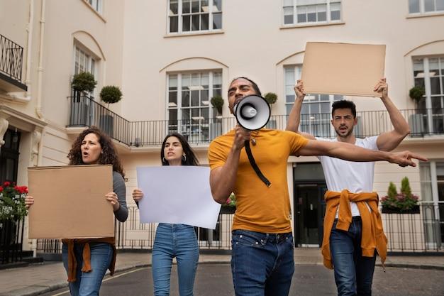 Ludzie protestujący z plakatami średni strzał