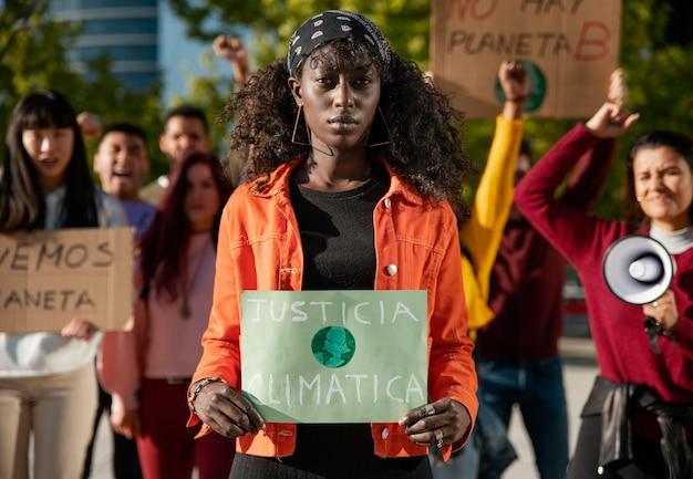 Ludzie protestujący z transparentami strzałami średnimi