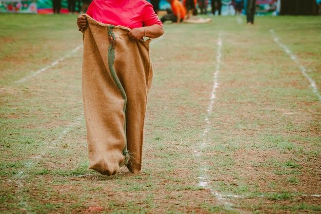 Ludzie prowadzący worek wyścigowy w polu w kulturze wsi