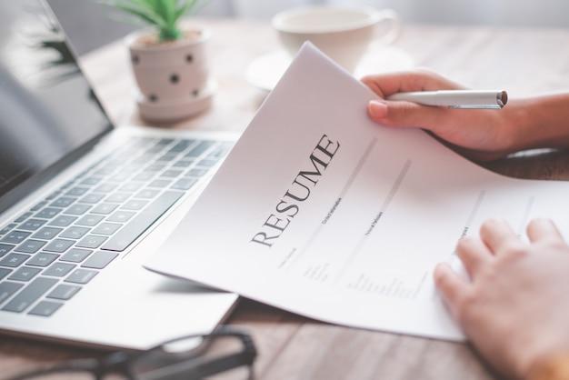Ludzie przeglądają podania o pracę przed wypełnieniem cv na formularzu podania o pracę, aby ubiegać się o pracę w firmie.