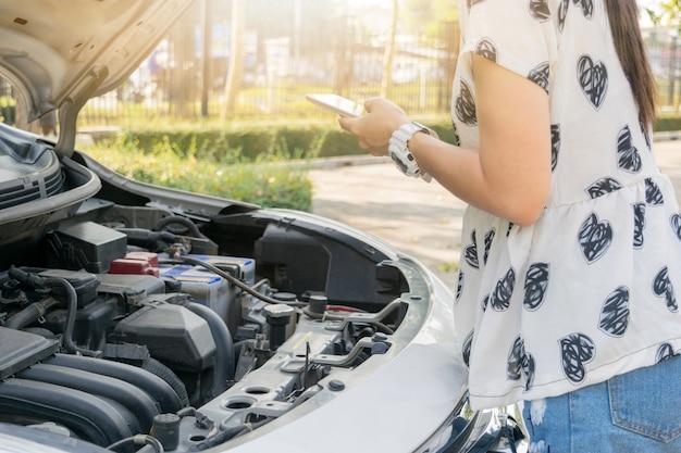 Ludzie przeglądający samochody silnikowe i używają smartfonów
