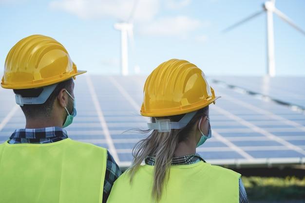 Ludzie przemysłowi pracujący w elektrowni słonecznej w maskach ochronnych
