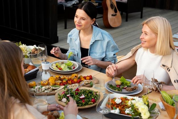 Ludzie przy stole z pysznym jedzeniem z bliska