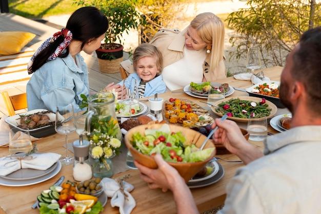 Ludzie przy stole ze smacznym jedzeniem z bliska