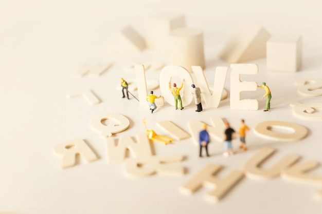 Ludzie przygotowujący walentynki z tekstem miłość i stonowanym delikatnym pastelowym kolorem.