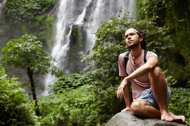 Ludzie, przyroda i przygoda. młody hipster z plecakiem siedzi na dużej skale przy wodospadzie