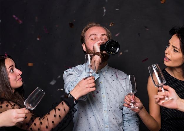 Ludzie pytają o szampana, podczas gdy człowiek pije z butelki