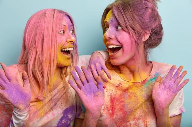 Ludzie, radość, koncepcja uroczystości. portret wesołych, radosnych młodych kobiet spoglądających na siebie radośnie, radujących się z najbardziej kolorowego wydarzenia w religii hinduskiej, aktywnie gestykulujących, z kolorowym proszkiem na ciele