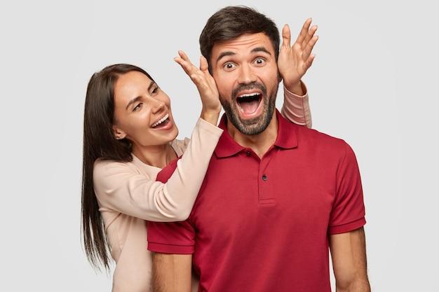 Ludzie, radość, przyjemny moment w życiu. uszczęśliwiona brunetka europejska młoda kobieta stoi obok swojego chłopaka, zakrywa oczy i robi niespodziankę, wspólnie się bawiąc, odizolowani na białej ścianie.