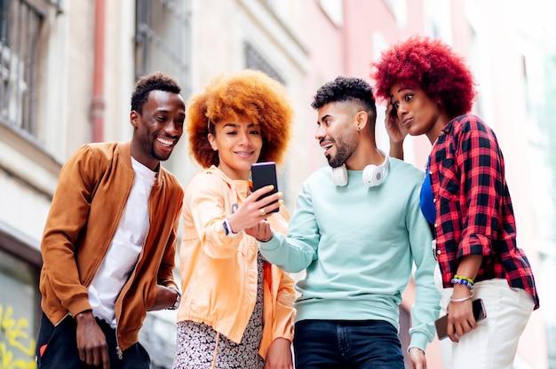 Ludzie razem patrzą na gestykulujący telefon komórkowy
