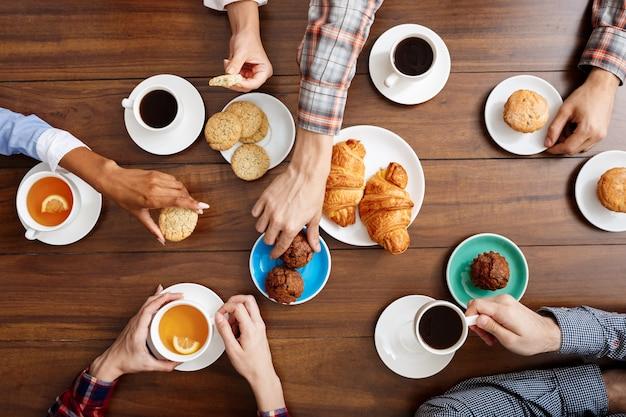 Ludzie ręce na drewnianym stole z rogalikami i kawą.