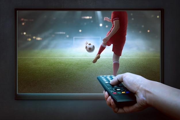 Ludzie ręce ze zdalnym oglądaniem meczu piłki nożnej