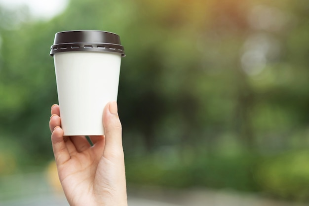 Ludzie ręka trzyma papierowy kubek na wynos picie kawy pokaż na jasnym niebie błękitnym naturalnym porannym słońcu.