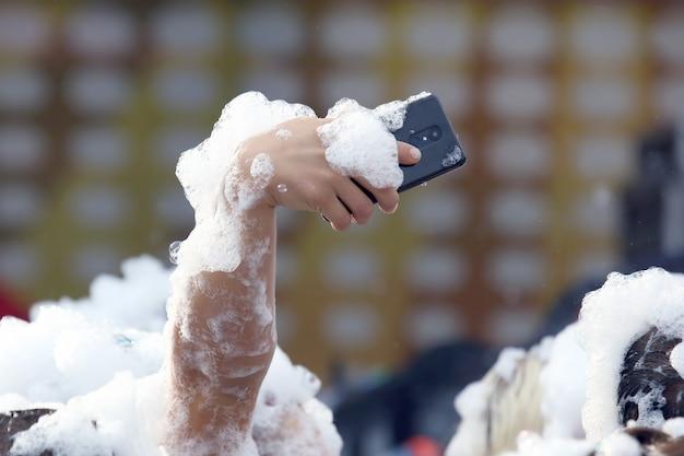 Ludzie robią sobie zdjęcia telefonem komórkowym na dyskotece mydlanej