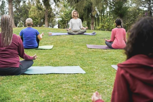 Ludzie robią zajęcia jogi, utrzymując dystans społeczny w parku miejskim