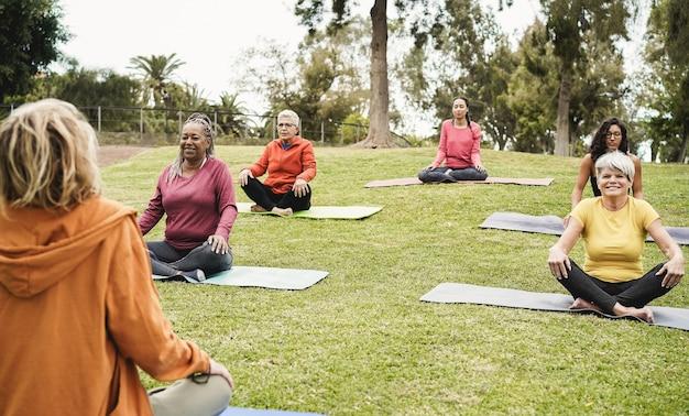 Ludzie robią zajęcia jogi, utrzymując dystans w parku miejskim