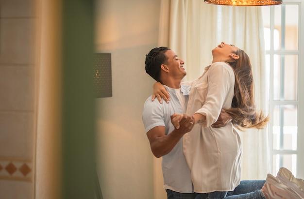 Ludzie romantyczny styl życia. piękna młoda para w swobodnym ubraniu tańczy i uśmiecha się stojąc w domu - związek i miłość z zabawą i nowym domem - para cieszy się mieszkaniem