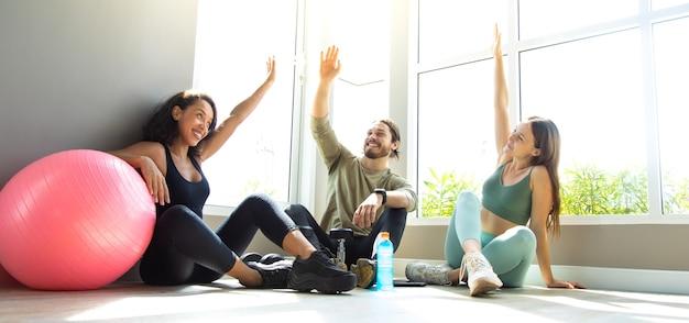 Ludzie rozmawiają i śmieją się razem szczęśliwi po treningu na siłowni. zdrowy styl życia i koncepcje sportowe.