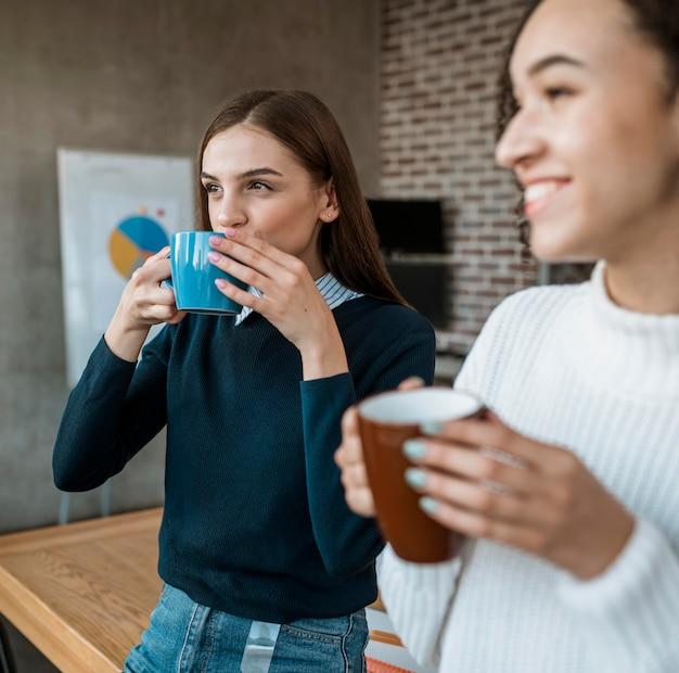 Ludzie rozmawiają ze sobą przy kawie podczas spotkania w biurze