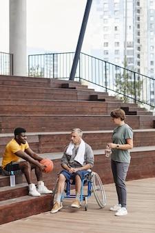 Ludzie rozmawiają ze sportowcem na stadionie