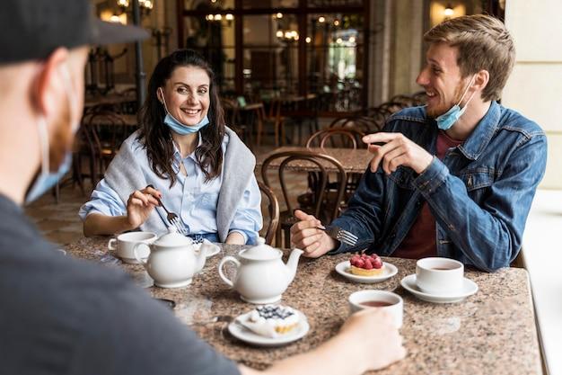 Ludzie rozmawiający w restauracji z maskami na twarz