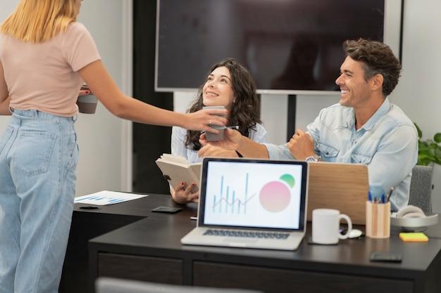Ludzie rozmawiający w tle w coworkingu, podczas gdy na pierwszym planie pojawia się komputer