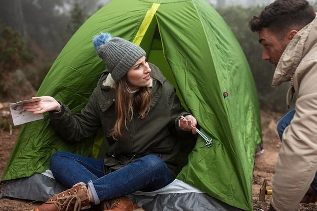 Ludzie rozmawiający z mapą i namiotem