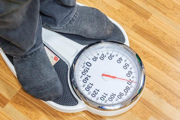 Ludzie są ważeni na wadze wagi przed corocznym badaniem fizykalnym