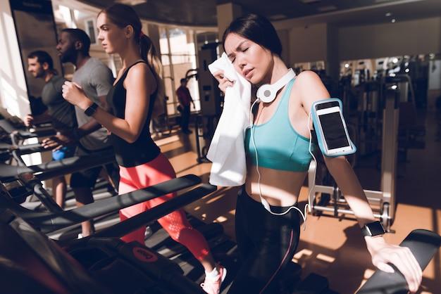 Ludzie są zaangażowani w bieżnie w nowoczesnej siłowni.