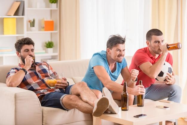 Ludzie siedzą na kanapie i razem oglądają piłkę nożną.