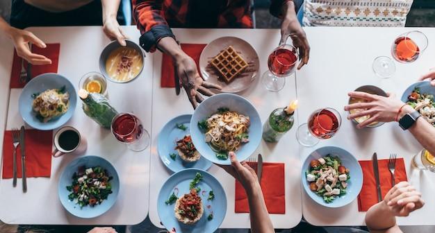 Ludzie siedzą przy stole i jedzą. widok z góry.