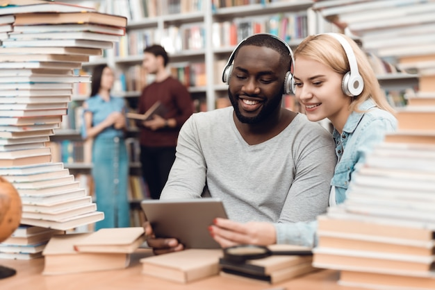 Ludzie siedzą przy stole w otoczeniu książek w bibliotece.