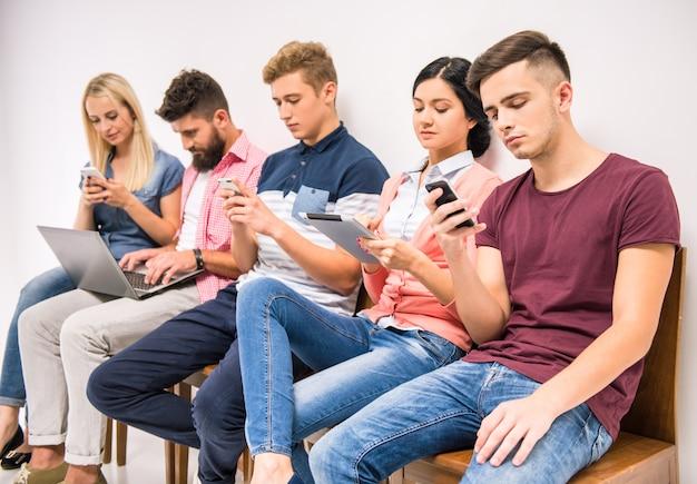 Ludzie siedzą w holu i patrzą na telefony.