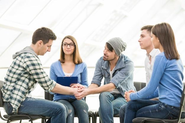 Ludzie siedzą w kręgu i wspierają się nawzajem.