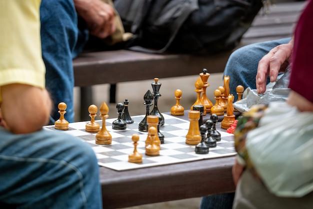 Ludzie siedzą w parku na ławkach i grają w szachy.