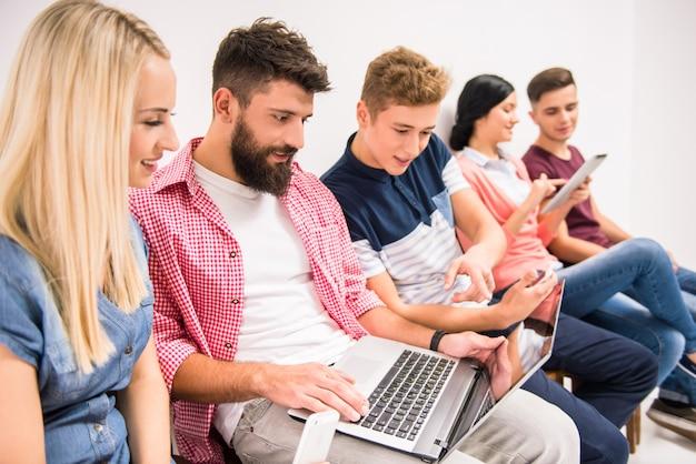 Ludzie siedzą w rzędzie i klikają laptopa.
