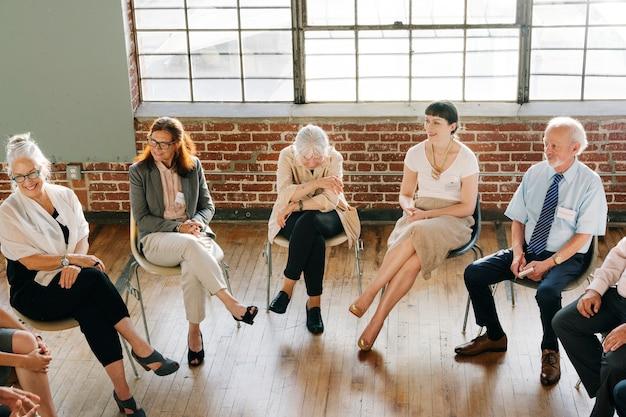 Ludzie siedzący i rozmawiający z grupą