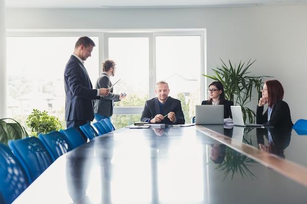 Ludzie siedzący przy stole w sali konferencyjnej