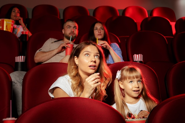 Ludzie siedzący w kinie z popcornem i napojami