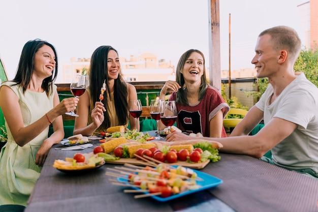 Ludzie śmieją się i trzyma napoje na imprezie
