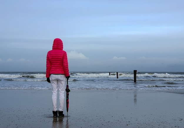 Ludzie spacerujący nad morzem pod zachmurzonym niebem