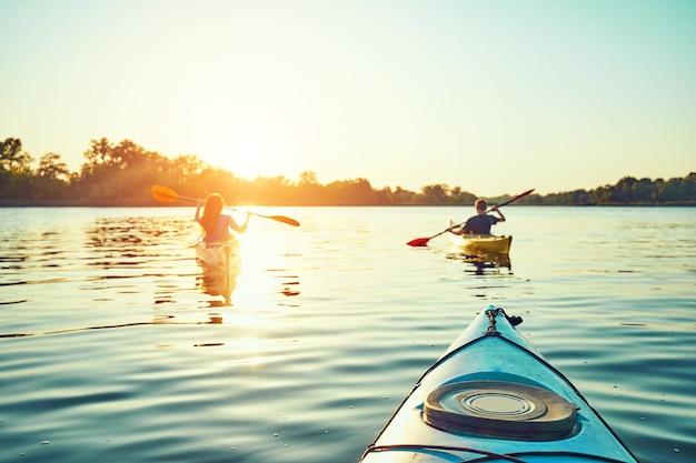 Ludzie spływają kajakiem podczas zachodu słońca w tle. baw się dobrze w wolnym czasie.