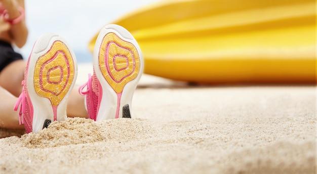 Ludzie, sport i zdrowy tryb życia. zamknij widok podeszwy kobiecych butów do biegania. młoda sportsmenka po odpoczynku na świeżym powietrzu, siedząc na plaży po intensywnych ćwiczeniach cardio. płytka śmierć pola
