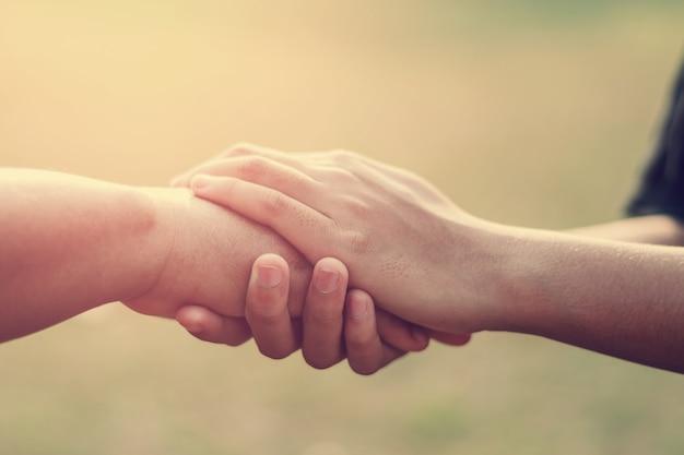 Ludzie starzy i młodzi ręki mienia z zmierzchu tłem